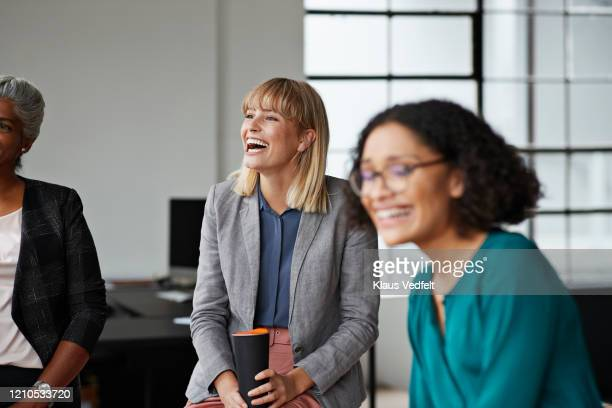 excited businesswoman looking away in office - employee engagement stock pictures, royalty-free photos & images