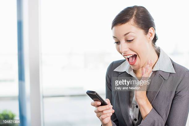 Excited businesswoman reading text message on cell phone