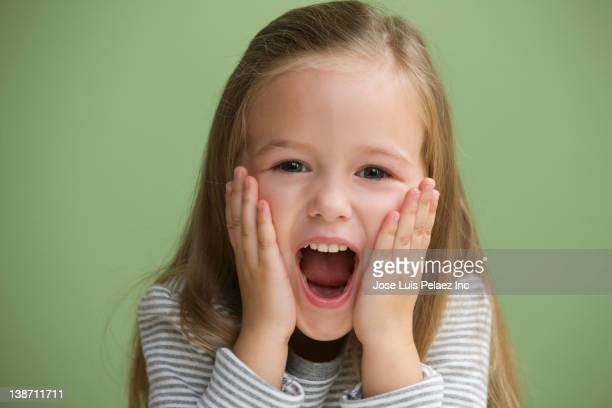 Excited Caucasian girl with head in hands