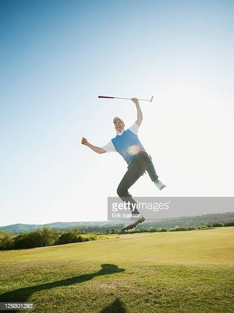 Excited Caucasian golfer jumping in mid-air on golf course
