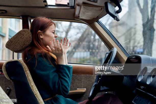 Excited Caucasian woman driving car