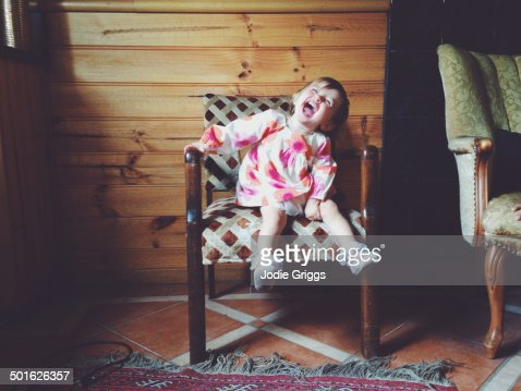 Excited child sitting on a chair being silly