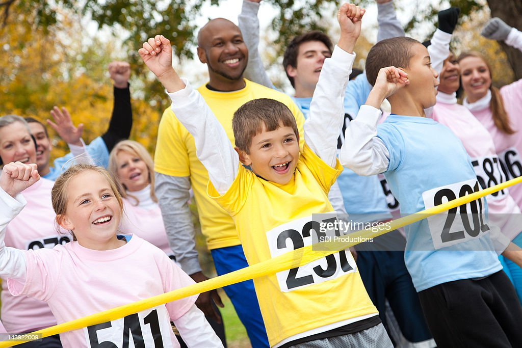 Excited children and adults happily crossing a race finish line : Stock Photo