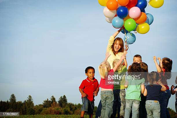 Excited Children Reaching for Balloons