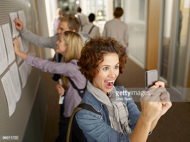Excited college student looking at cell phone in corridor