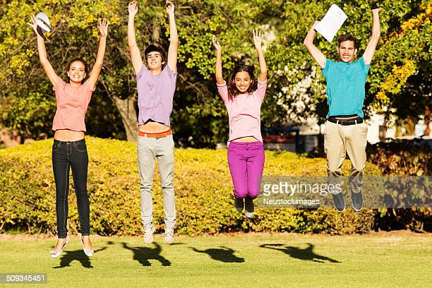 excited college students with exam results jumping on campus - day stock pictures, royalty-free photos & images