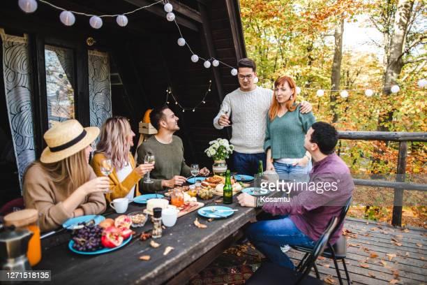 couples excités annonçant qu'ils attendent le bébé, pendant la réunion avec leurs meilleurs amis - annonce grossesse photos et images de collection