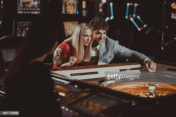 Excited couple  gambling at electronic roulette in casino