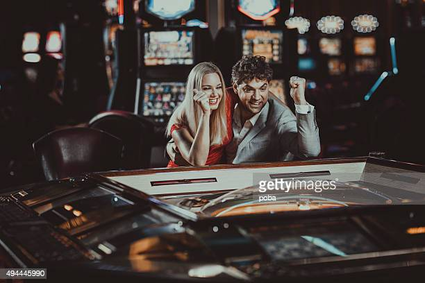 excited couple  gambling at electronic roulette in casino - casino stock pictures, royalty-free photos & images