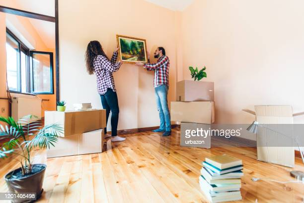 excited couple hanging picture on wall - hanging stock pictures, royalty-free photos & images