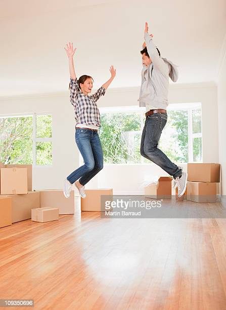 Excited couple jumping in new house