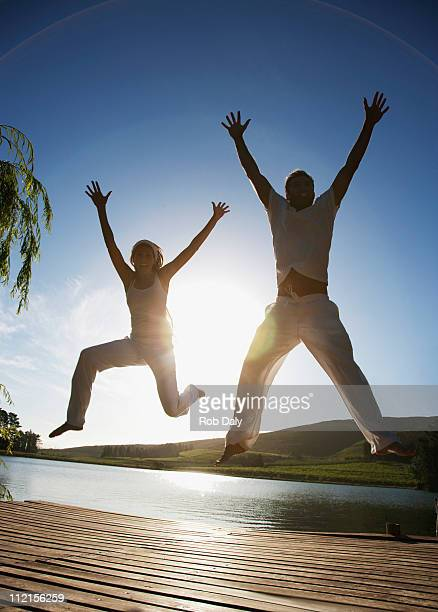 excited couple jumping on beach - woman straddling man stock pictures, royalty-free photos & images