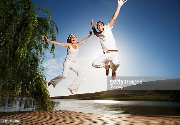 excited couple jumping on pier - barefoot stock pictures, royalty-free photos & images