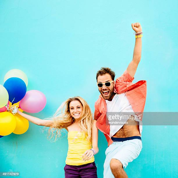 Excited couple jumping with balloons
