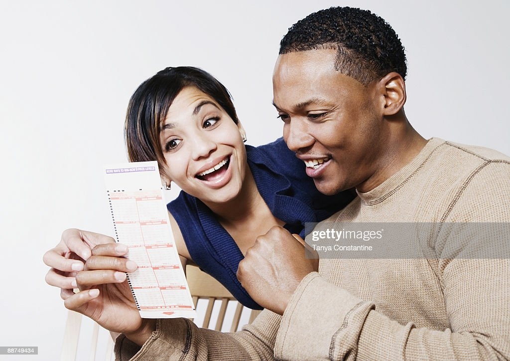 Excited couple looking at lottery ticket : Stock Photo