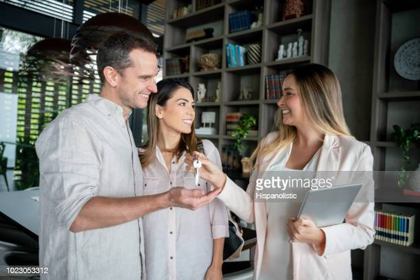 excited couple receiving the keys from their real estate agent all looking very happy and smiling - lease agreement stock pictures, royalty-free photos & images