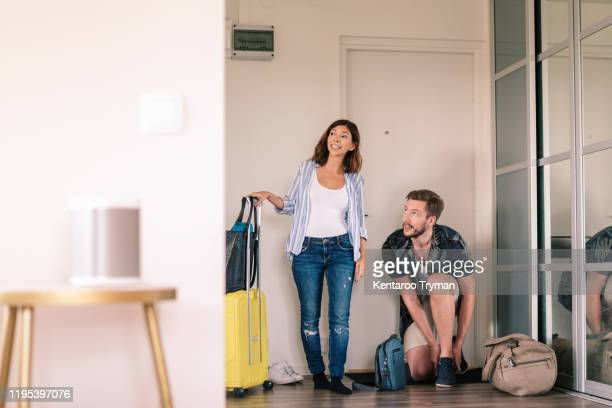 excited couple with luggage removing shoes while looking around in apartment against doorway - strip stock pictures, royalty-free photos & images