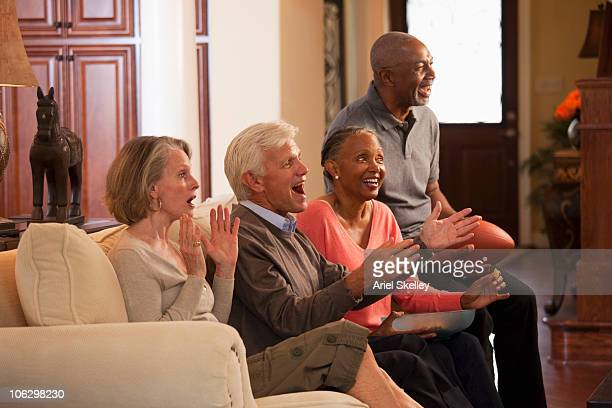 excited couples watching football on tv on living room sofa - old american football stock photos and pictures