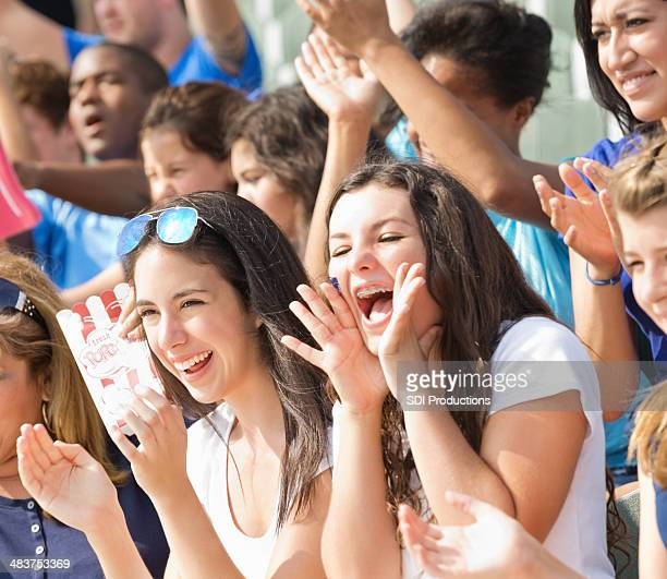 excited crowd of fans cheering on team from stadium bleachers - american football sport stock photos and pictures