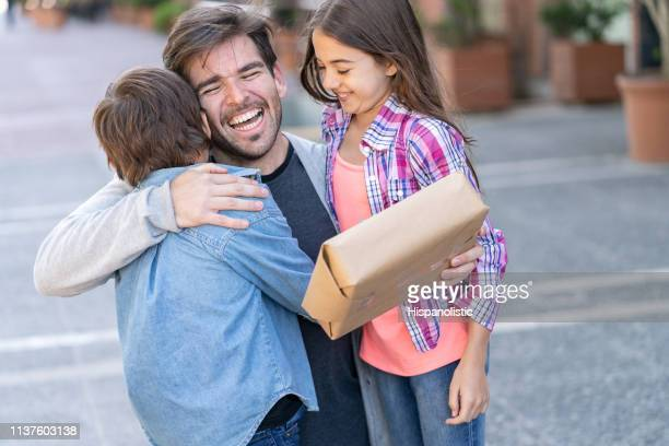 excited daddy hugging son and daughter after they surprise him with a gift for fathers day - dia dos pais imagens e fotografias de stock