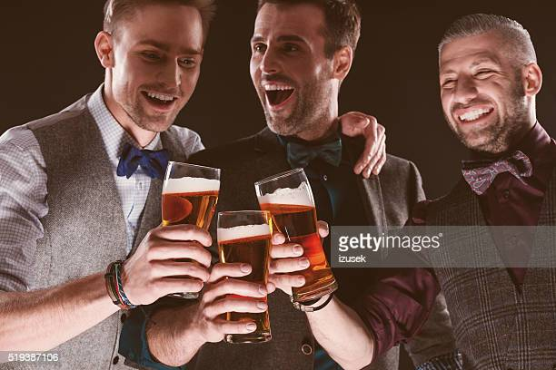 Excited elegant businessmen toasting with beer in nightclub