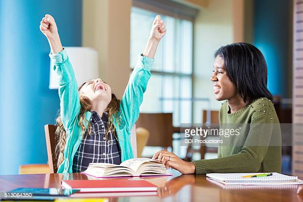 Excited elementary girl celebrating while doing homework with tutor