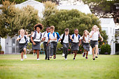Excited Elementary School Pupils Wearing Uniform Running Across Field At Break Time