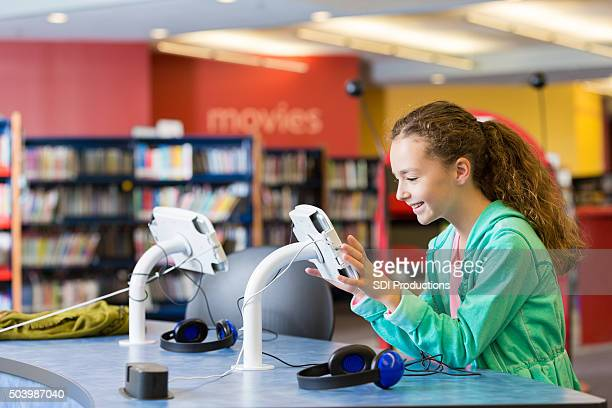 Excited elementary student using new digital tablet technology in library