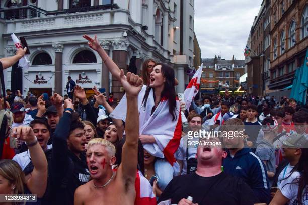 Excited England supporters sing and chant in Leicester Square ahead of the England vs Italy Euro 2020 football final match.