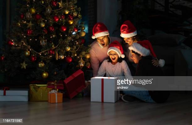 excited family opening christmas gifts at home - christmas family stock pictures, royalty-free photos & images