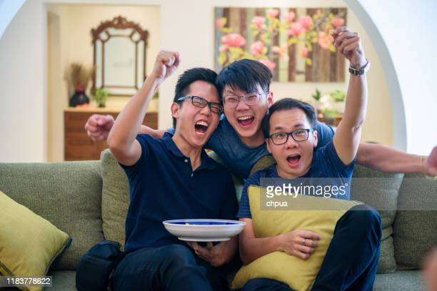 excited fans cheering for sport team watching game - champions league trophy stock pictures, royalty-free photos & images