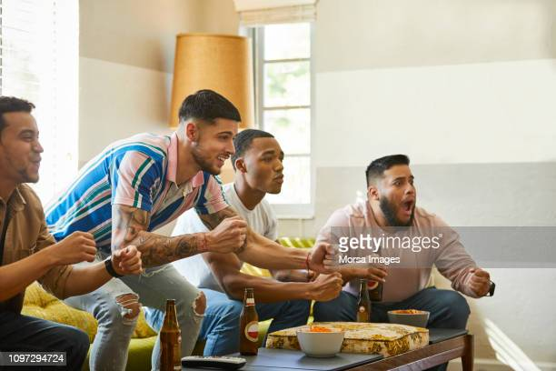 excited fans cheering while watching match at home - match sport stock pictures, royalty-free photos & images