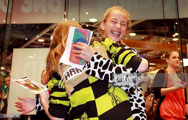 Excited fans hug each other inside the official One Direction merchandise store on April 20 2012 in Wellington New Zealand The 1D fan store will sell...