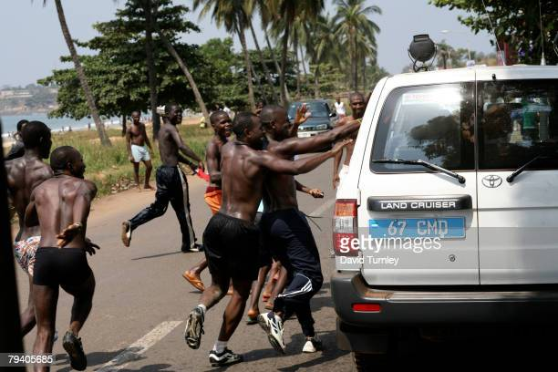 Excited fans interrupt their beachside football matches to greet UNICEF Goodwill Ambassador David Beckham as he is driven through the capital in a...