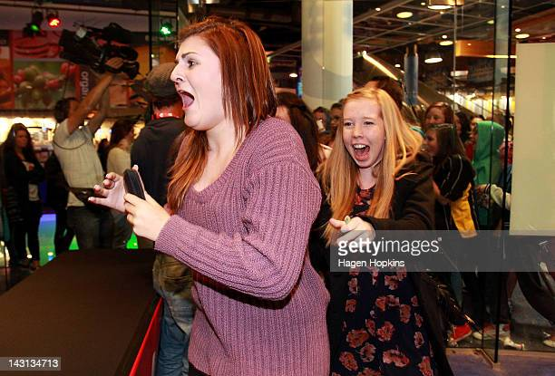 Excited fans rush into the official One Direction merchandise store as it opens on April 20 2012 in Wellington New Zealand The 1D fan store will sell...