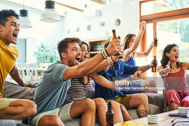 excited fans shouting while watching match on tv - watching stock pictures, royalty-free photos & images
