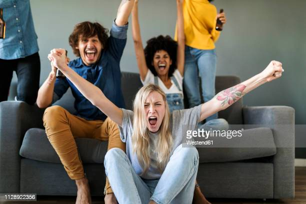 excited fans watching tv and cheering - vreugde stockfoto's en -beelden