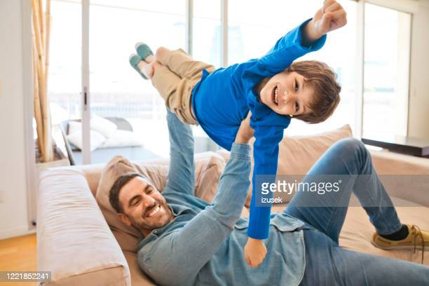 excited father and son enjoying time together during lockdown - diversity stock pictures, royalty-free photos & images