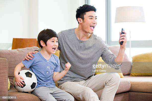 Excited father and son watching football on TV