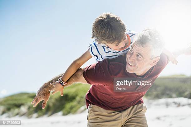Excited father giving piggyback to son at beach