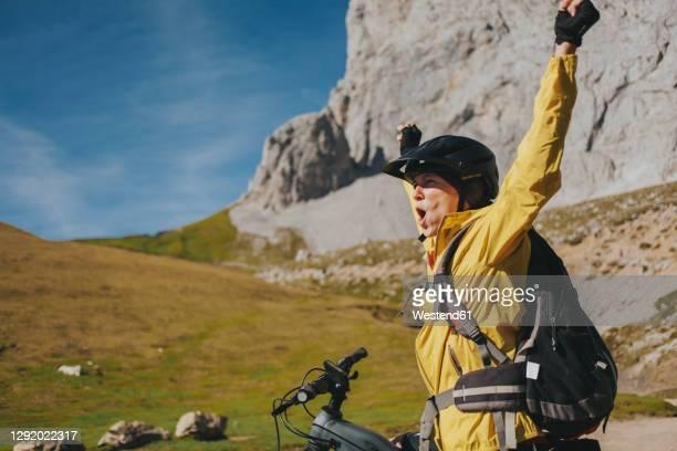 excited female cyclist with arms raised shouting at picos de europa national park on sunny day, cantabria, spain - cantabria fotografías e imágenes de stock