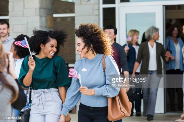 excited female friends leave polling place on election day - family politics stock pictures, royalty-free photos & images