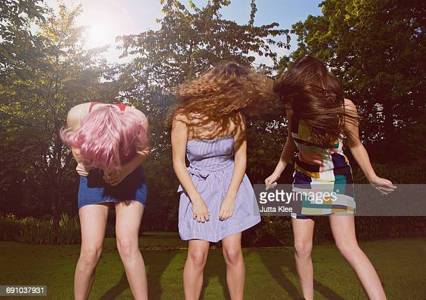 Excited female friends tossing hair at yard during sunny day