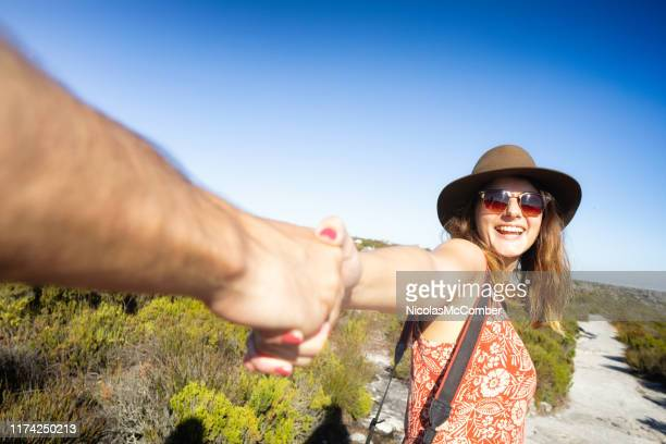 excited female pulls her male friend by the hand leading him - província do cabo ocidental imagens e fotografias de stock