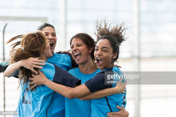 excited female soccer players hugging after scoring a goal - goal sports equipment stock pictures, royalty-free photos & images