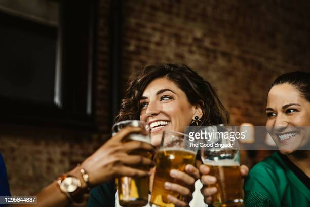excited female sports fans celebrating in bar at pub - honour stock pictures, royalty-free photos & images