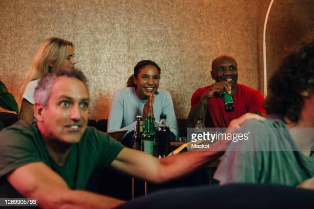 excited female teenager with hands clasped watching sports by family at home - spectator stock pictures, royalty-free photos & images