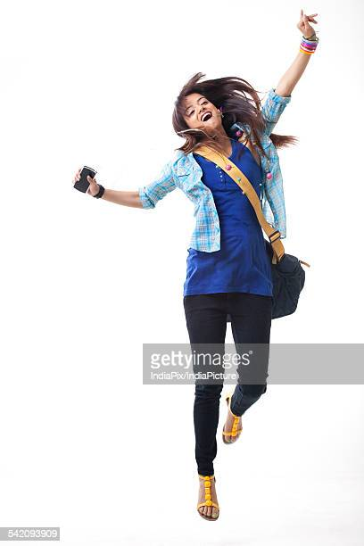 Excited female university student dancing while listening music on white background