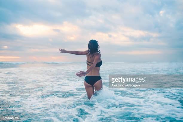 enthousiast vrouwtje met opgeheven armen gaat richting golvende oceaan - golf water stockfoto's en -beelden