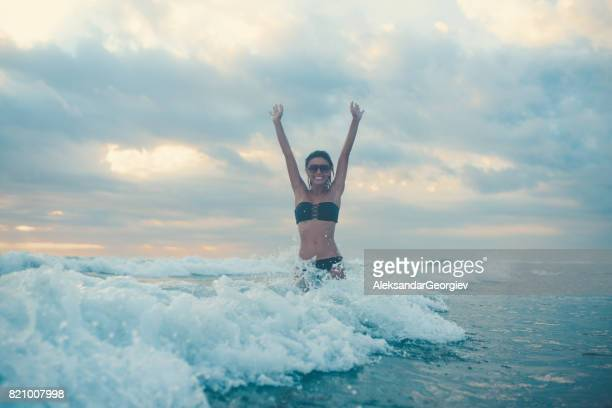 Excited Female with Raised Arms Jumping in Wavy Ocean